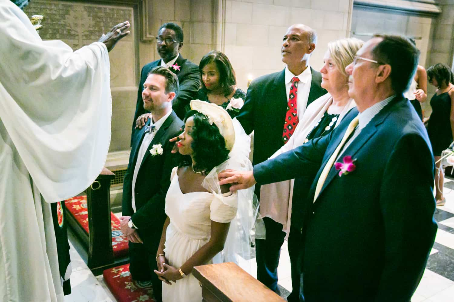 Guests with hands on bride and groom during Trinity Church wedding ceremony
