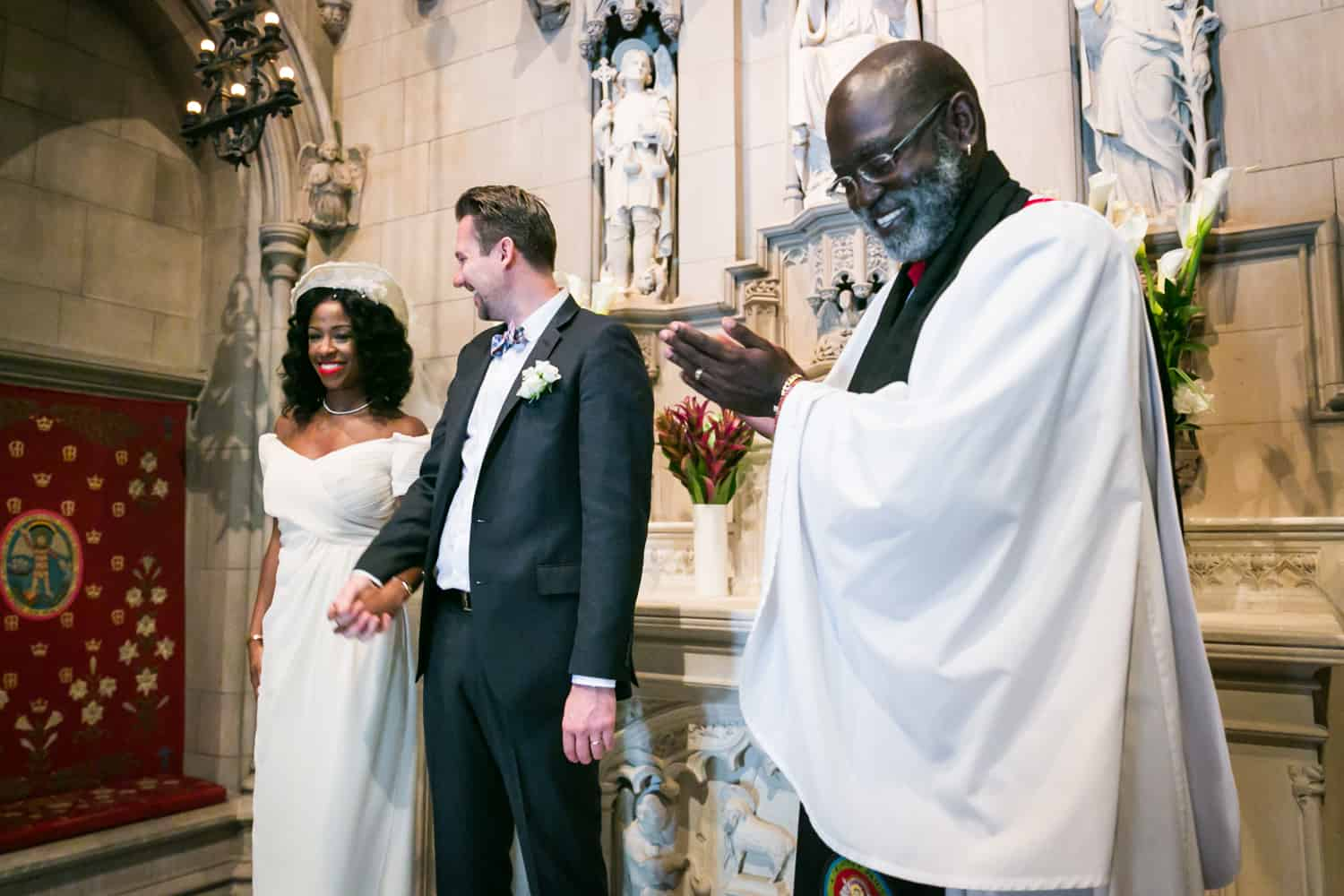 Priest clapping for bride and groom during Trinity Church wedding ceremony