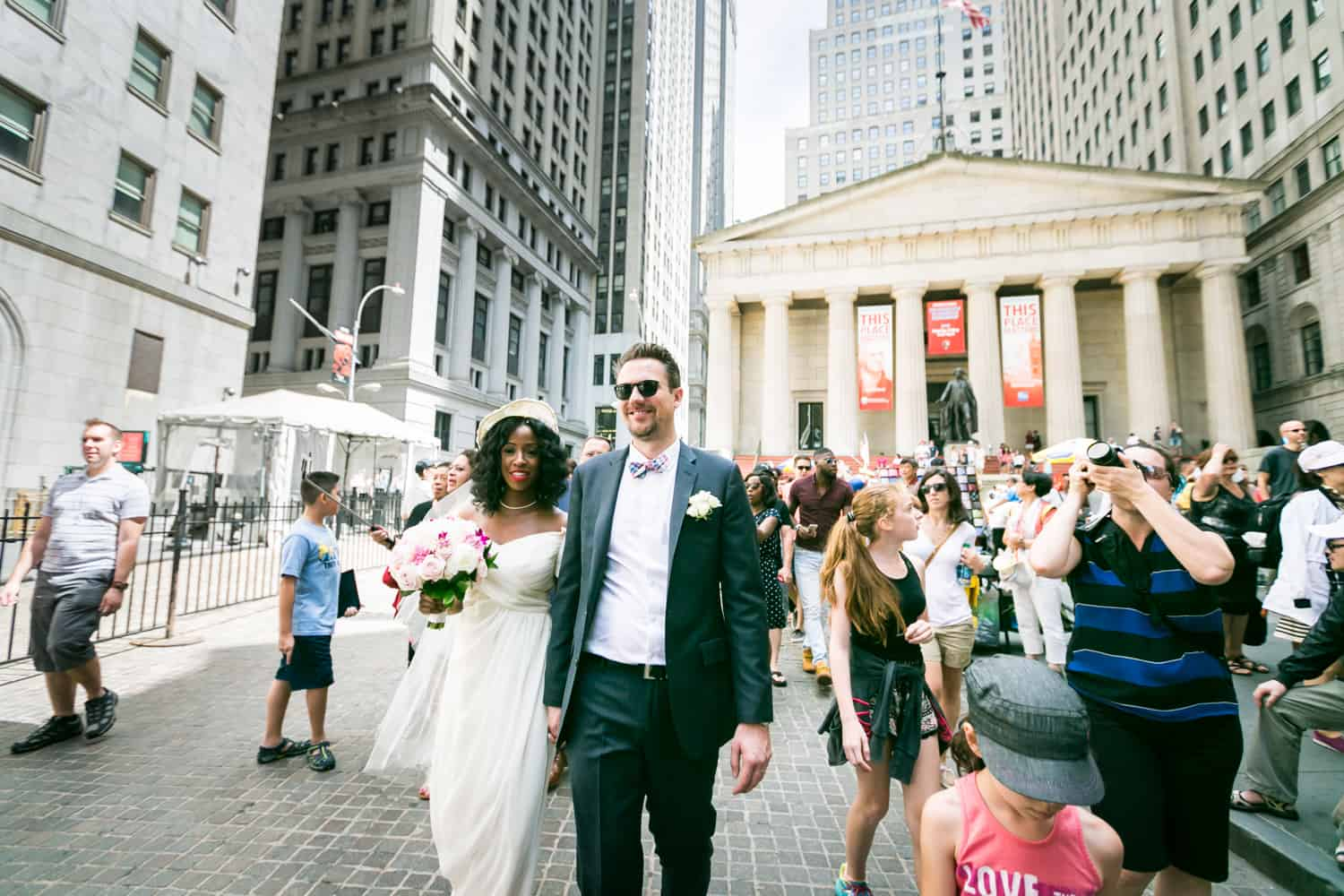 Bride and groom walking on Wall Street after Trinity Church ceremony