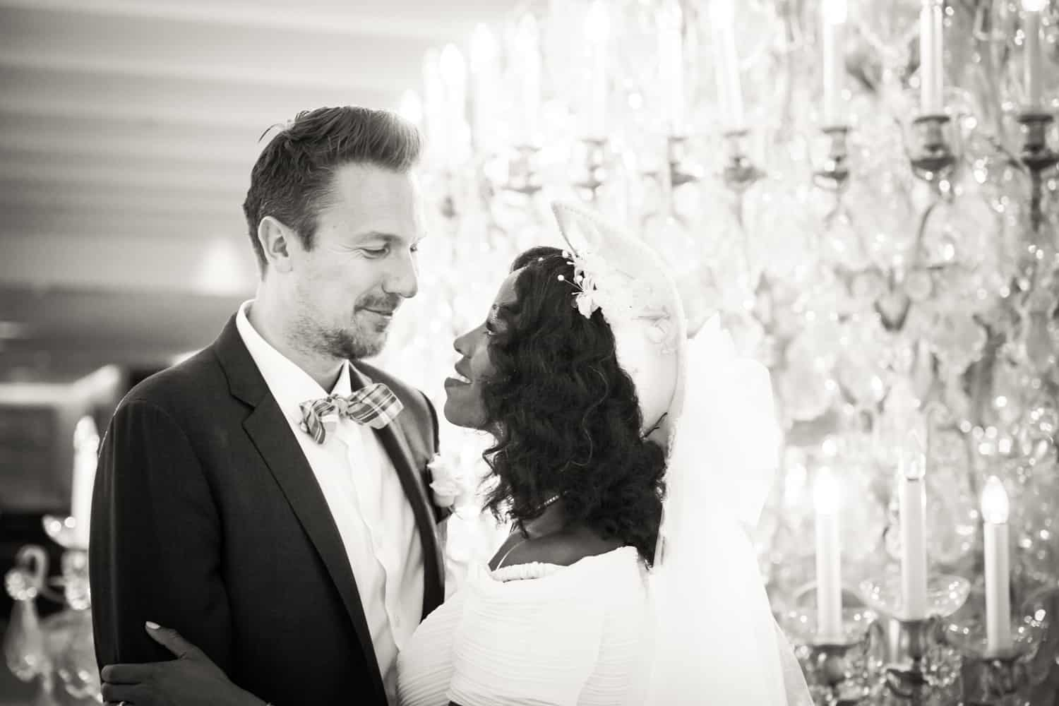 Black and white photo of bride and groom in front of chandelier