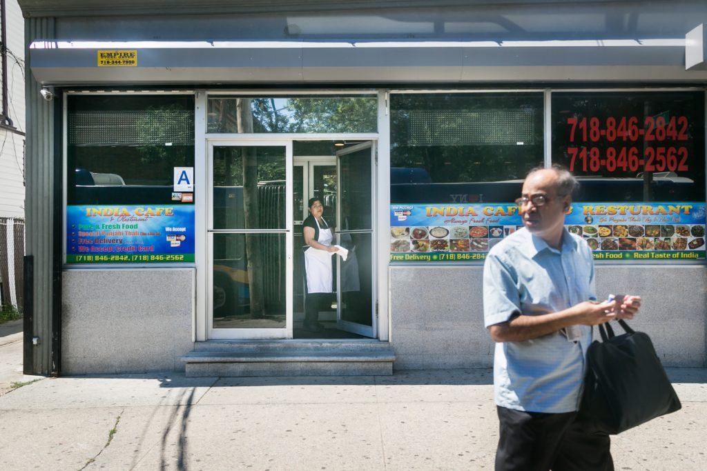 Man walking past storefront in Richmond Hill, Queens