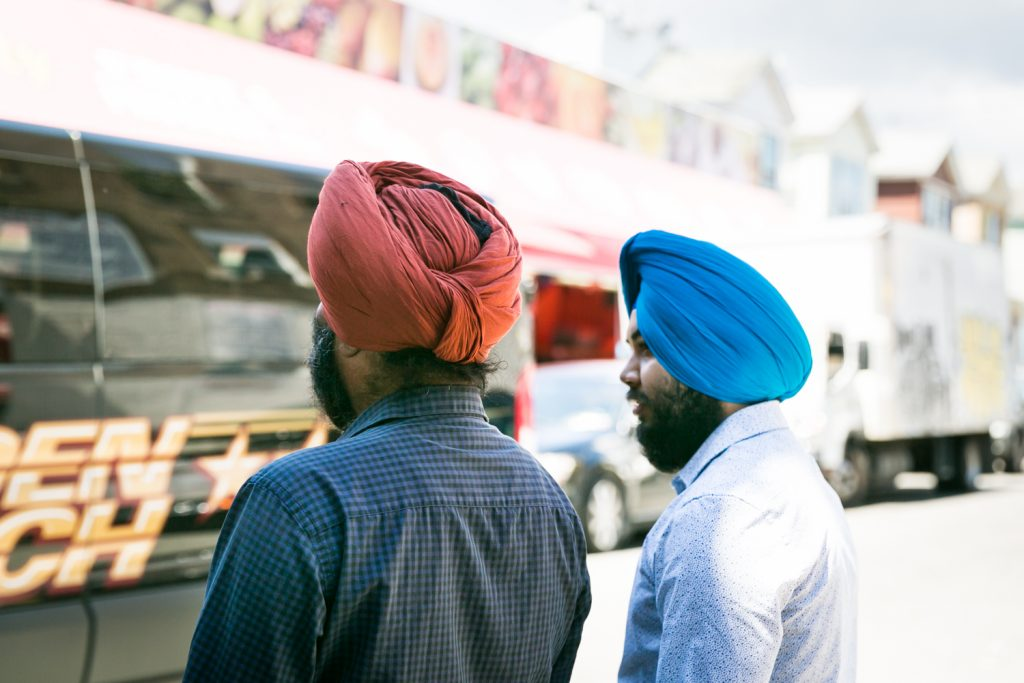 Two men wearing colored turbans on the streets of Richmond Hill, Queens