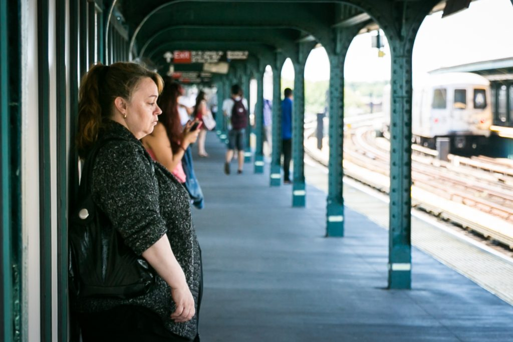 Woman staring ahead waiting for train in subway platform