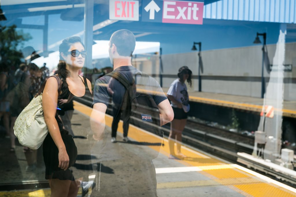 Couple in subway platform with reflection of woman waiting for train