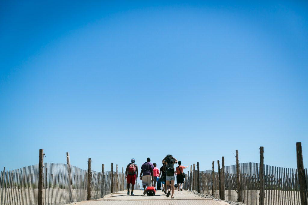 People walking down boardwalk to Far Rockaway beach