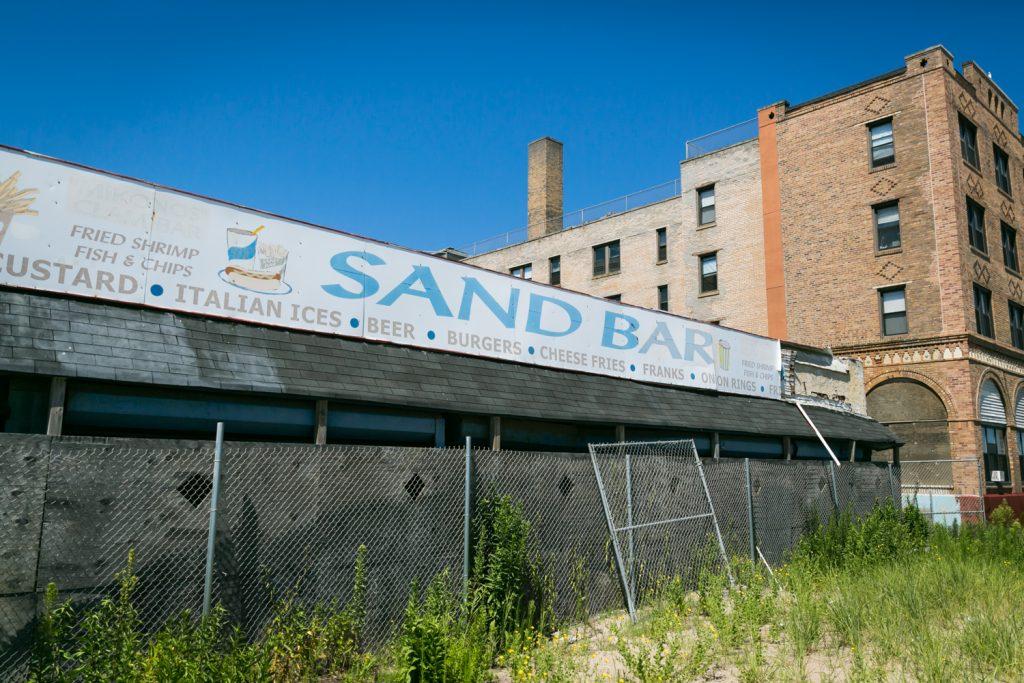 Sand Bar restaurant sign and fence in Far Rockaway
