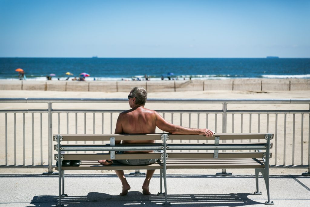 Older man sitting on bench on Far Rockaway beach boardwalk