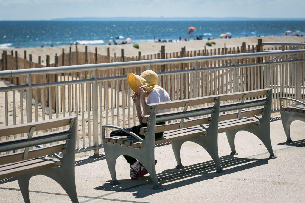 Woman holding onto hat on Far Rockaway beach boardwalk
