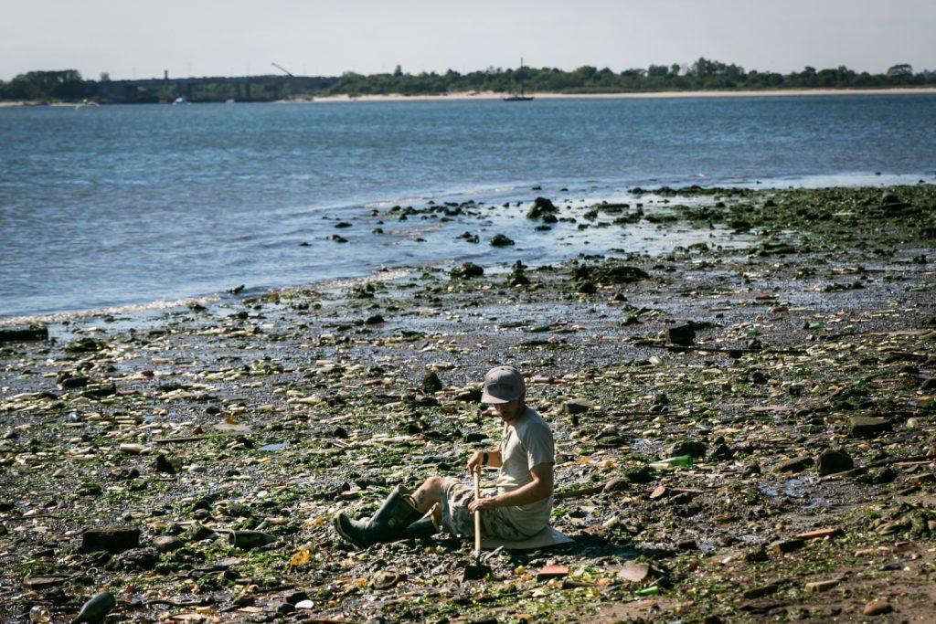 Dead Horse Bay photos of man digging on beach