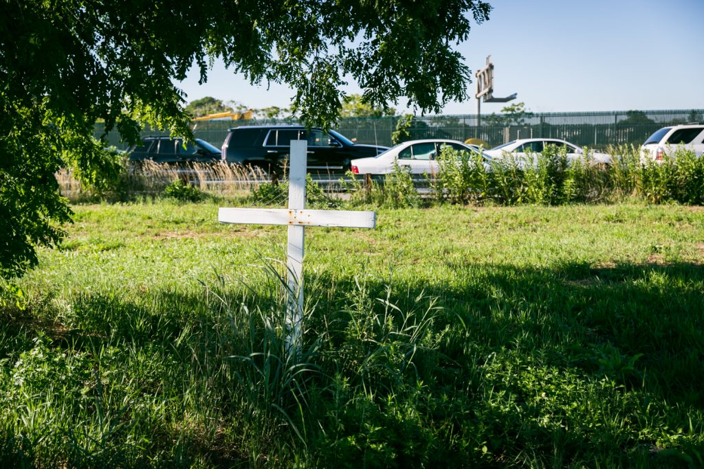 Dead Horse Bay photos of white cross in grass