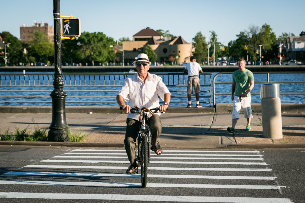 Old man wearing white hat and riding bicycle in crosswalk in Sheepshead Bay, Brooklyn