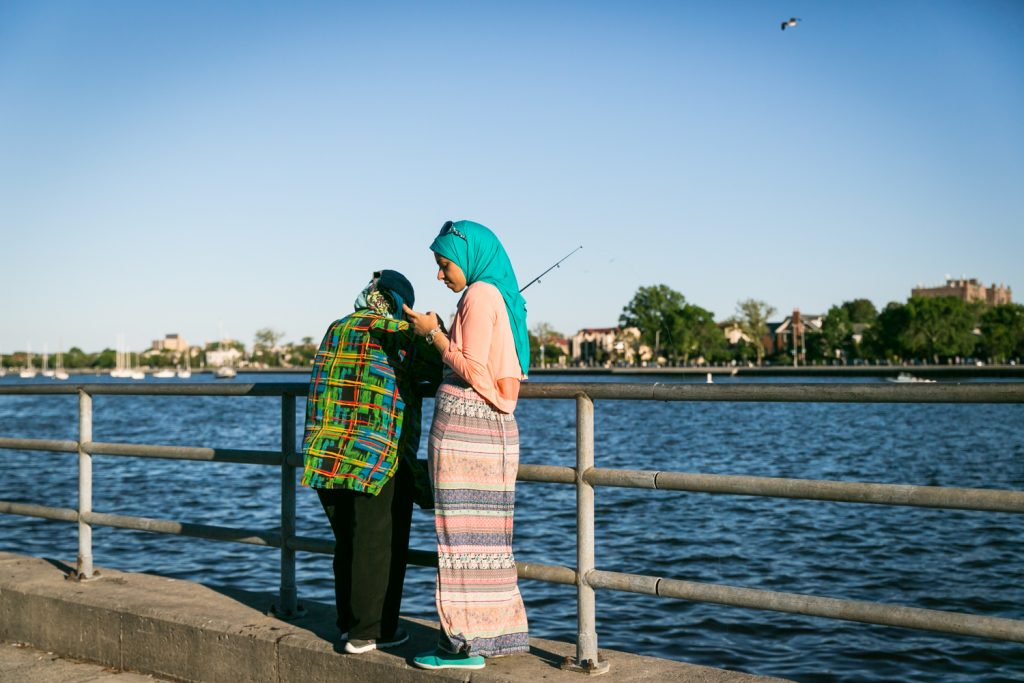 Muslim woman wearing blue hijab standing by waterfront railing in Sheepshead Bay, Brooklyn