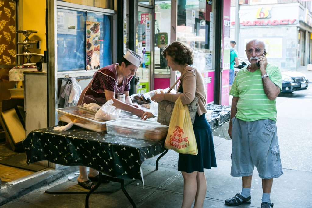 Woman buying from street vendor with man on cell phone in Sheepshead Bay, Brooklyn