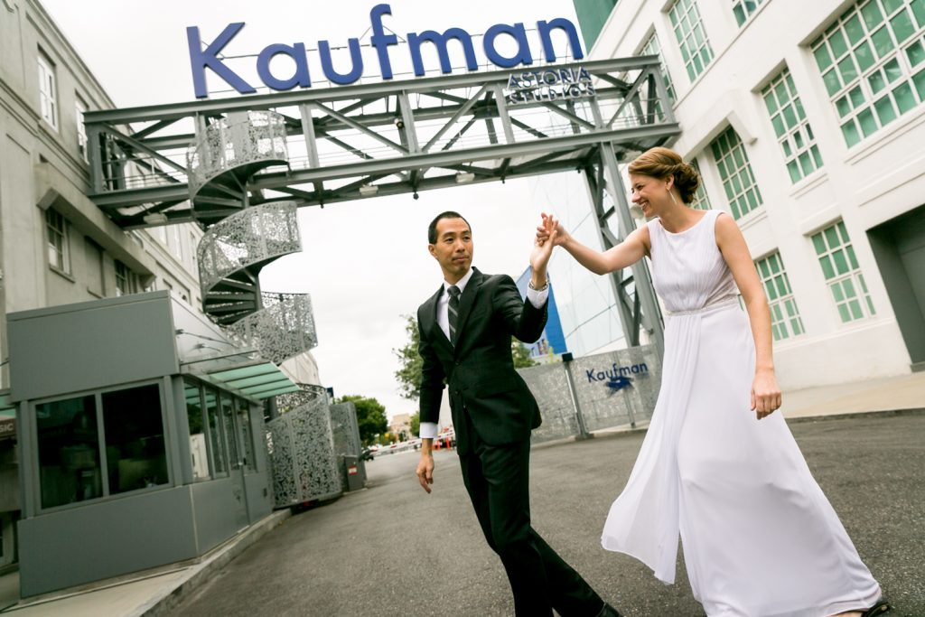 Bride and groom dancing underneath Kaufman Astoria Studios sign in Queens