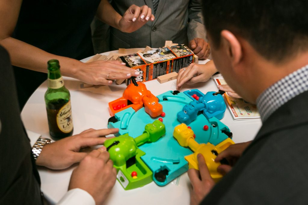 Close up on wedding guest hands playing Hungry Hungry Hippos game at a reception