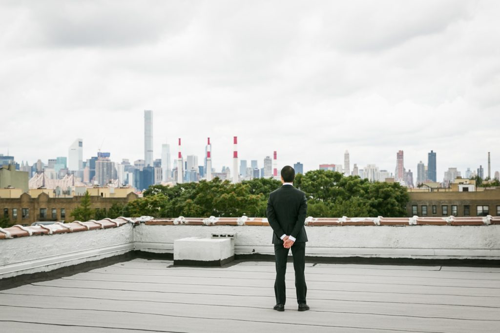 Groom turned around watching NYC skyline waiting for first look