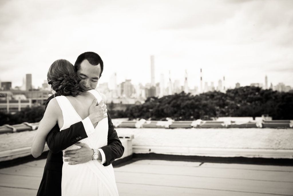 Black and white photo of bride and groom hugging after first look