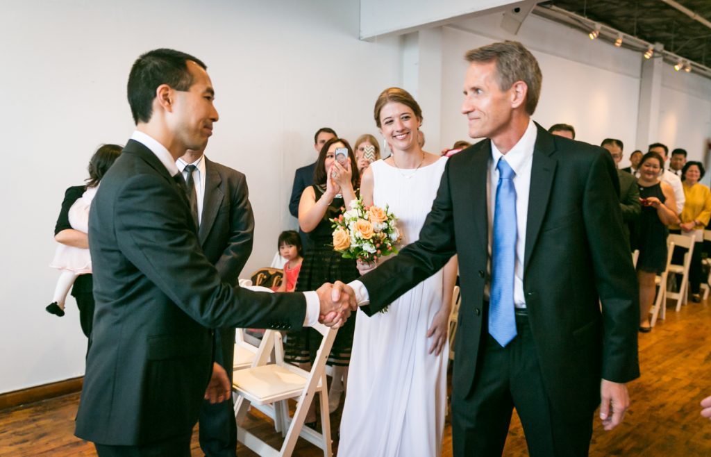 Groom shaking hand of father of the bride during Astoria wedding ceremony