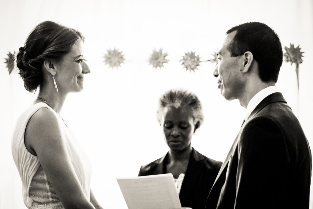Black and white photo of bride and groom saying vows during Astoria wedding ceremony