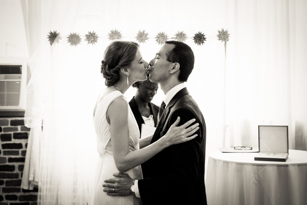 Black and white photo of bride and groom kissing after Astoria wedding ceremony