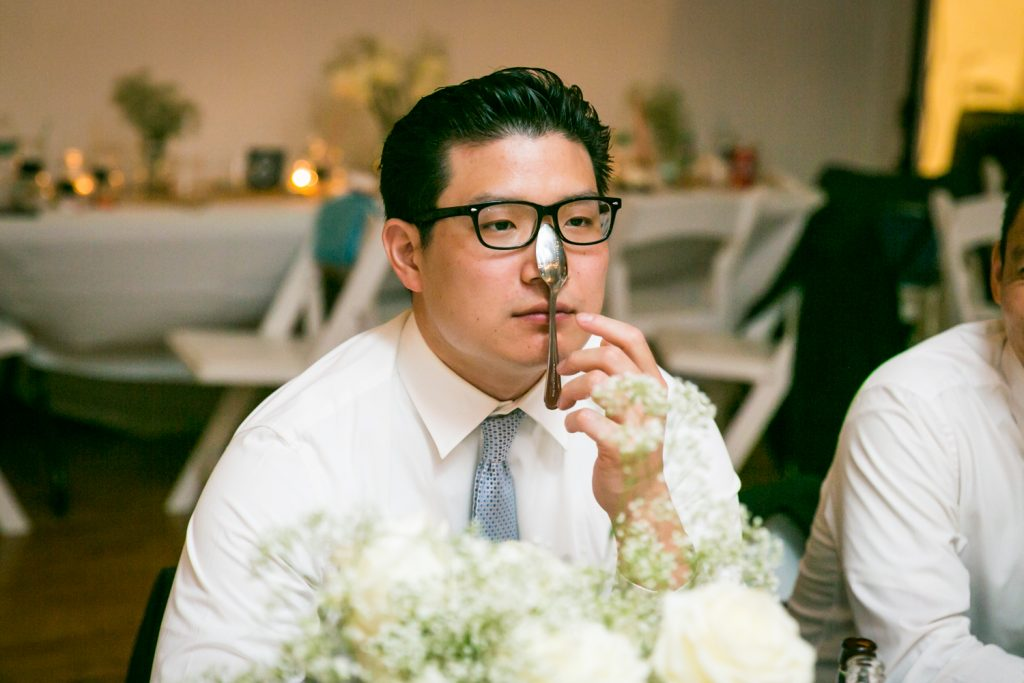 Wedding guest balancing spoon on his nose for an article on event entertainment ideas