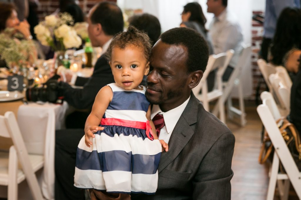 African American father holding little girl at Astoria wedding reception