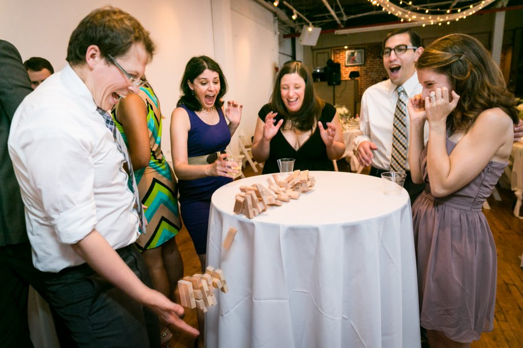Wedding guests watching a tower of Jenga blocks falling for an article on event entertainment ideas