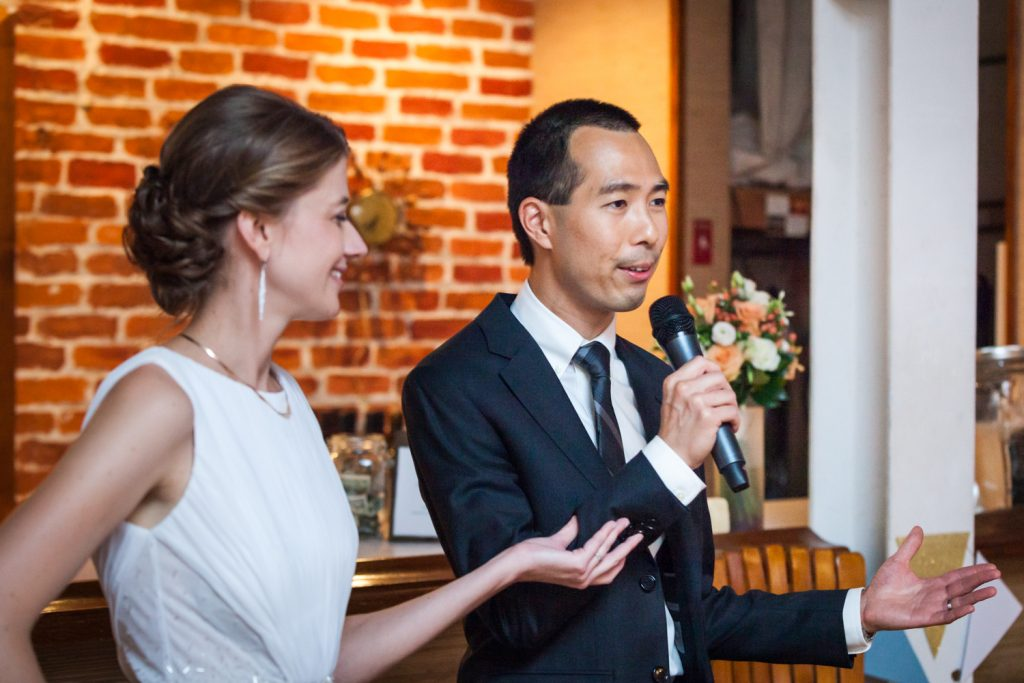 Bride holding groom's arm during speech at Astoria wedding reception