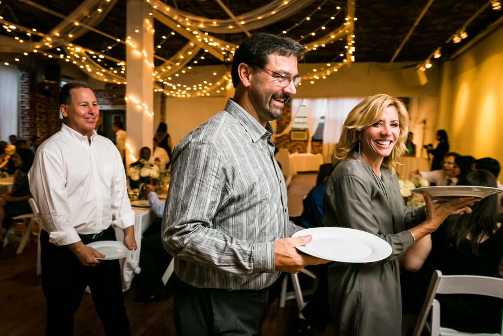 Guests in line at buffet holding plates at Astoria wedding reception