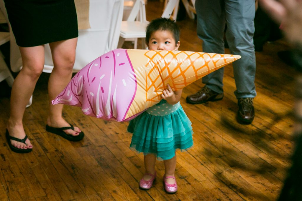 Little girl chewing on an inflated ice cream cone at Astoria wedding reception