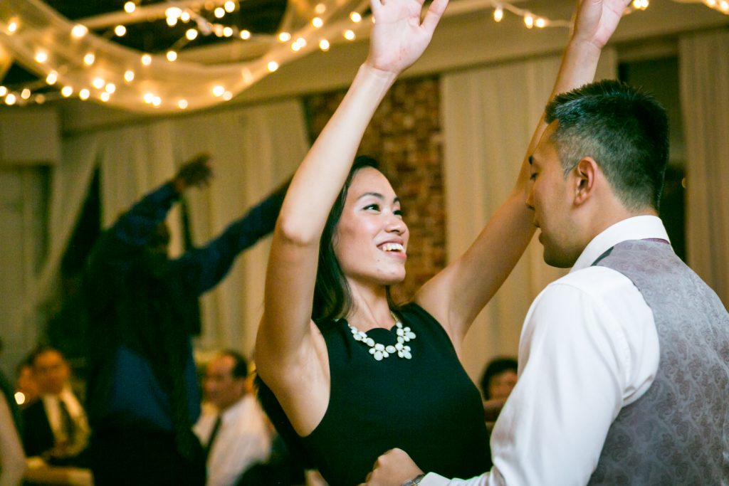 Female guest dancing with arms raised at Astoria wedding reception