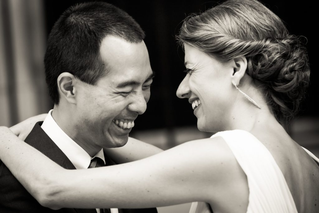 Black and white photo of bride and groom laughing at Astoria wedding reception
