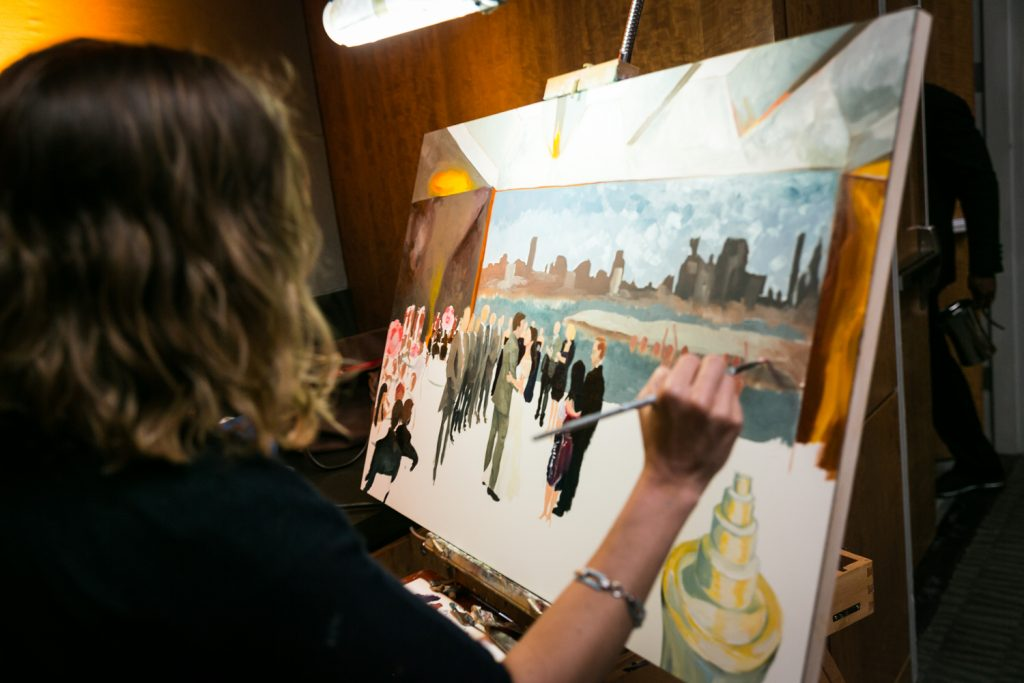 Artist painting canvas during wedding for an article on event entertainment ideas
