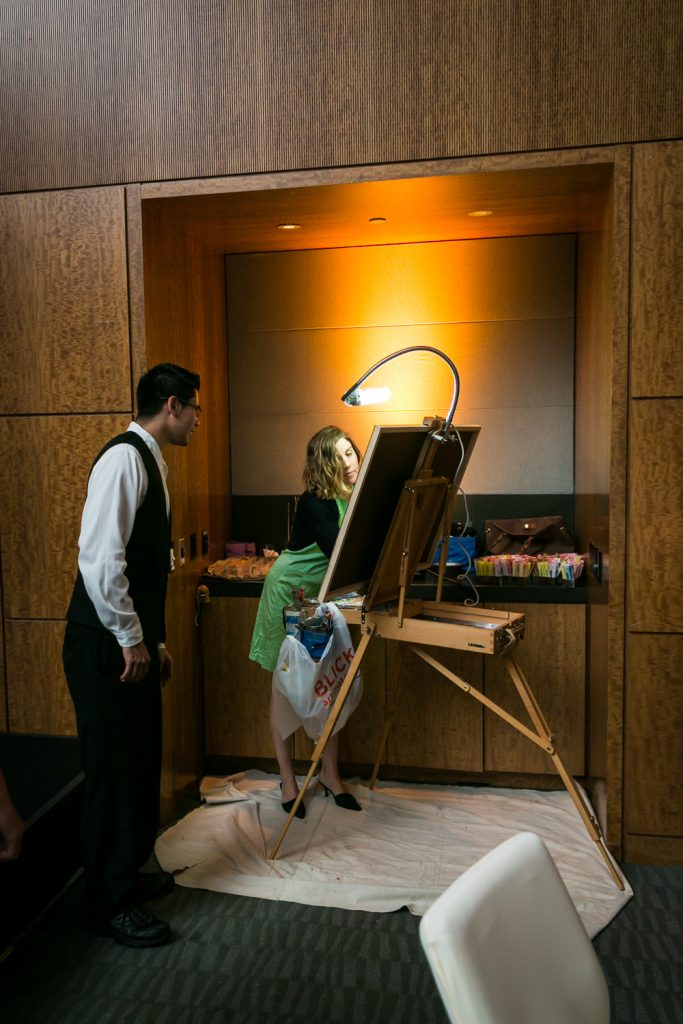 Guest watching as artist paints on an easel for an article on event entertainment ideas