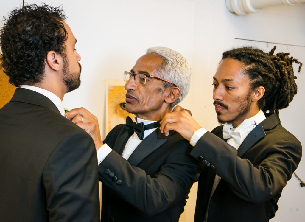 Groom adjusting collar of father, who is adjusting collar of best man