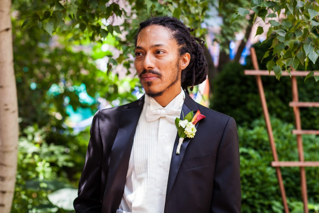 Portrait of groom with dreadlocks and wearing a tuxedo