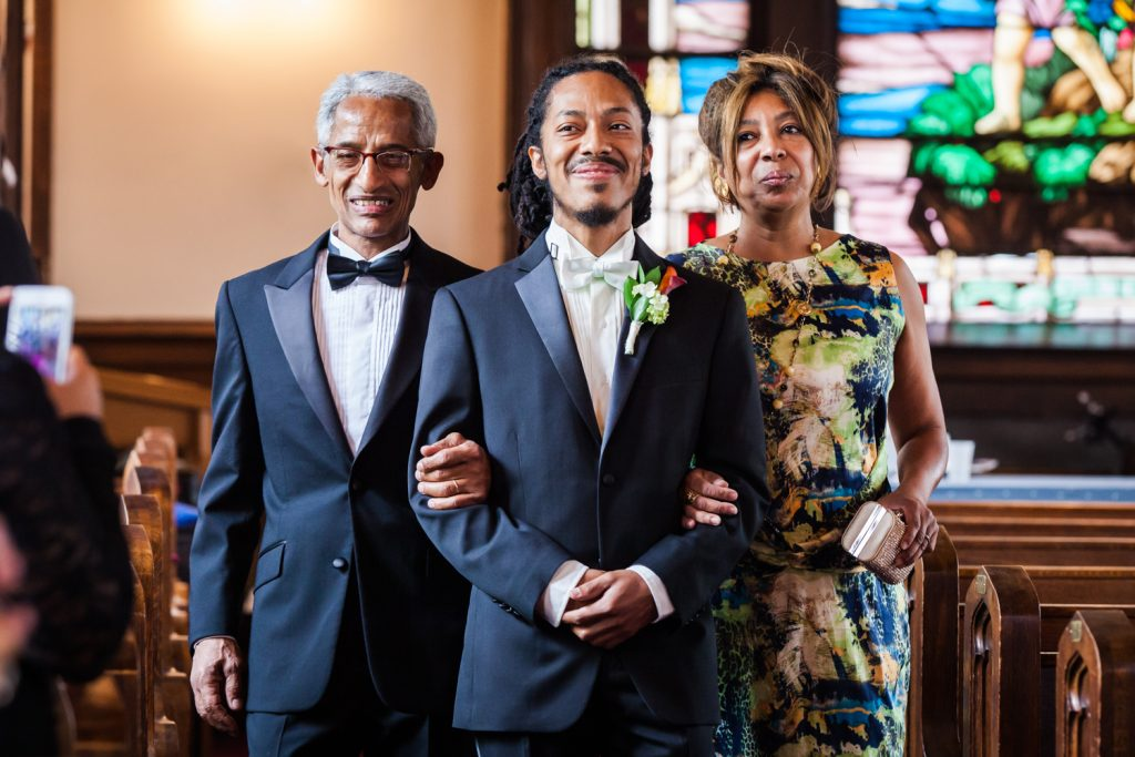 Groom walking down aisle of church with both parents