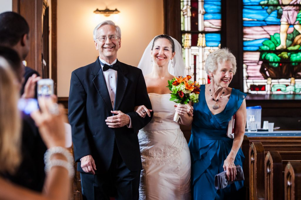 Bride walking down aisle of church with both parents