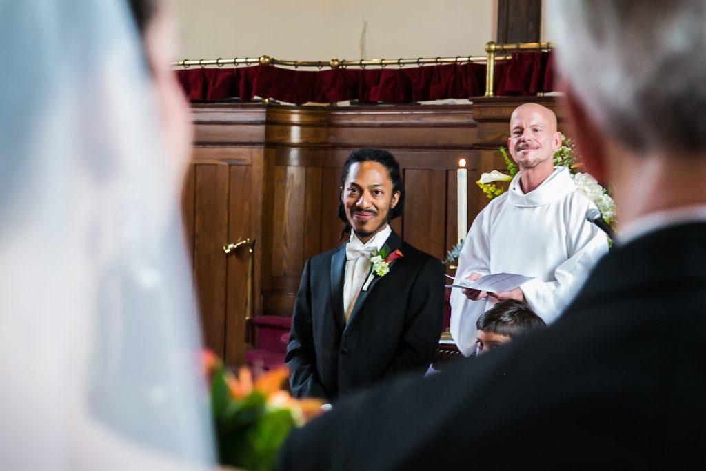 View of bride's shoulder of groom at altar