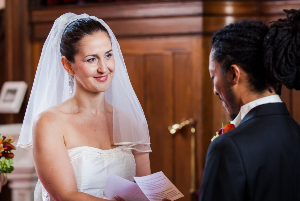 Bride listening to groom recite his vows at a DUMBO Loft wedding