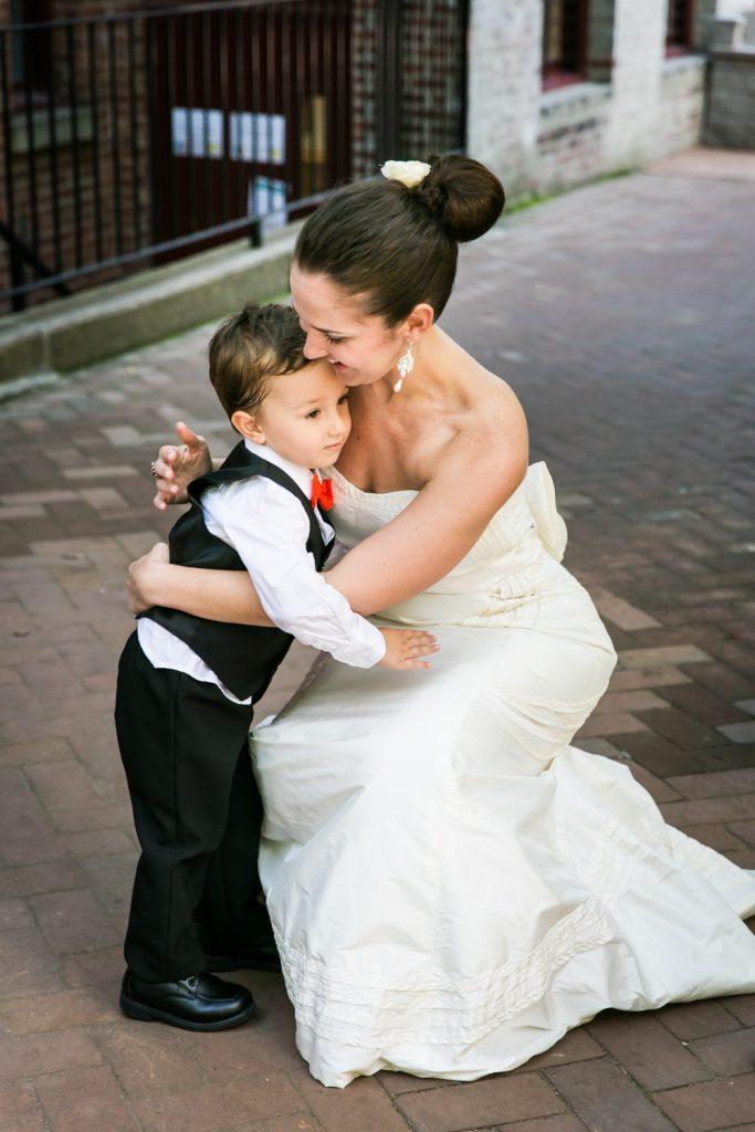 Bride bending down to hug a little boy at a DUMBO Loft wedding