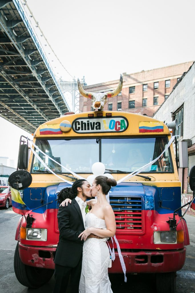Bride and groom kissing in front of chiva loca bus at a DUMBO Loft wedding