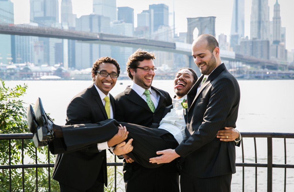 Groomsmen holding up groom for portrait in Brooklyn Bridge Park
