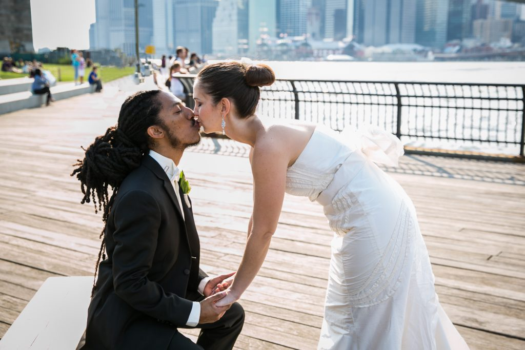 Bride bending down to kiss groom sitting on a bench