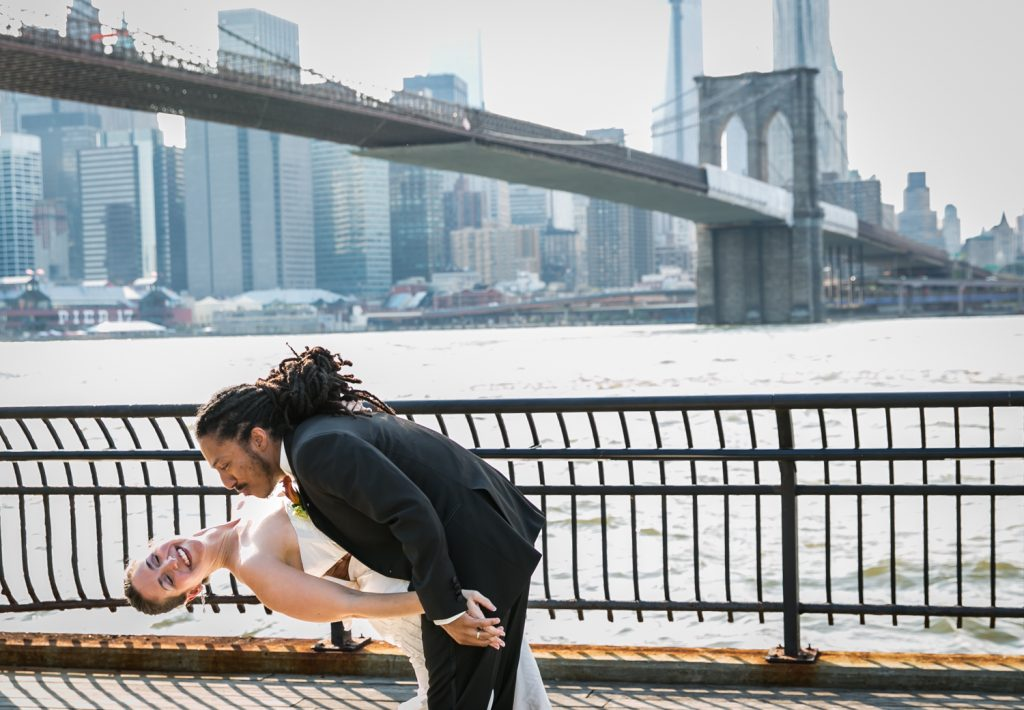 Groom dipping bride at Brooklyn Bridge Park for article on how to get the perfect first dance photos