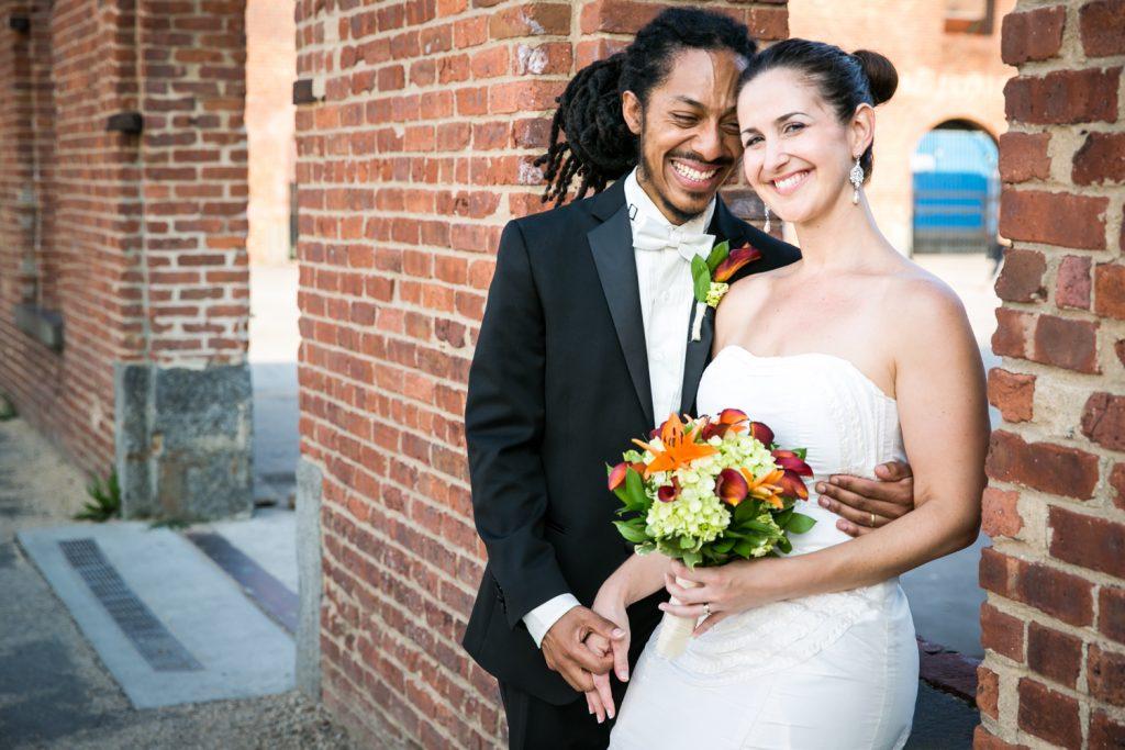 Portrait of bride and groom against brick background in Brooklyn Bridge Park