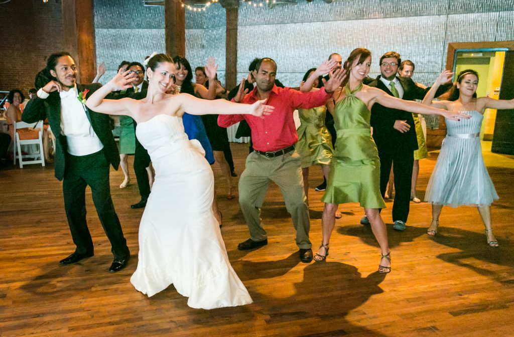 Bride and guests dancing with arms raised at a DUMBO Loft wedding