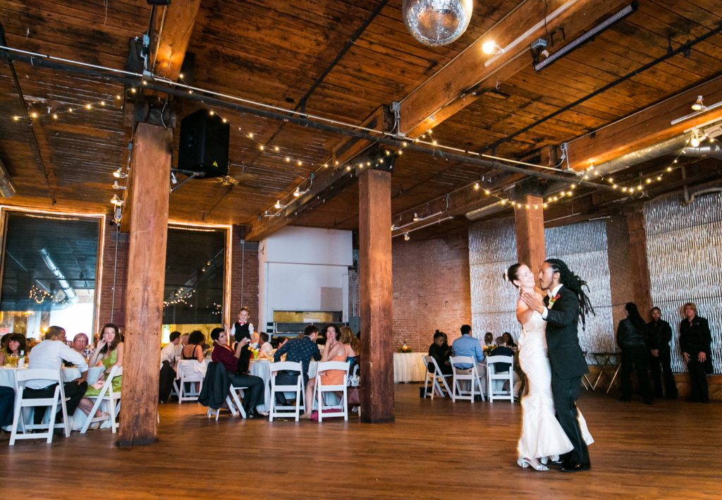 Bride and groom dancing alone on wide dance floor for article on how to get the perfect first dance photos