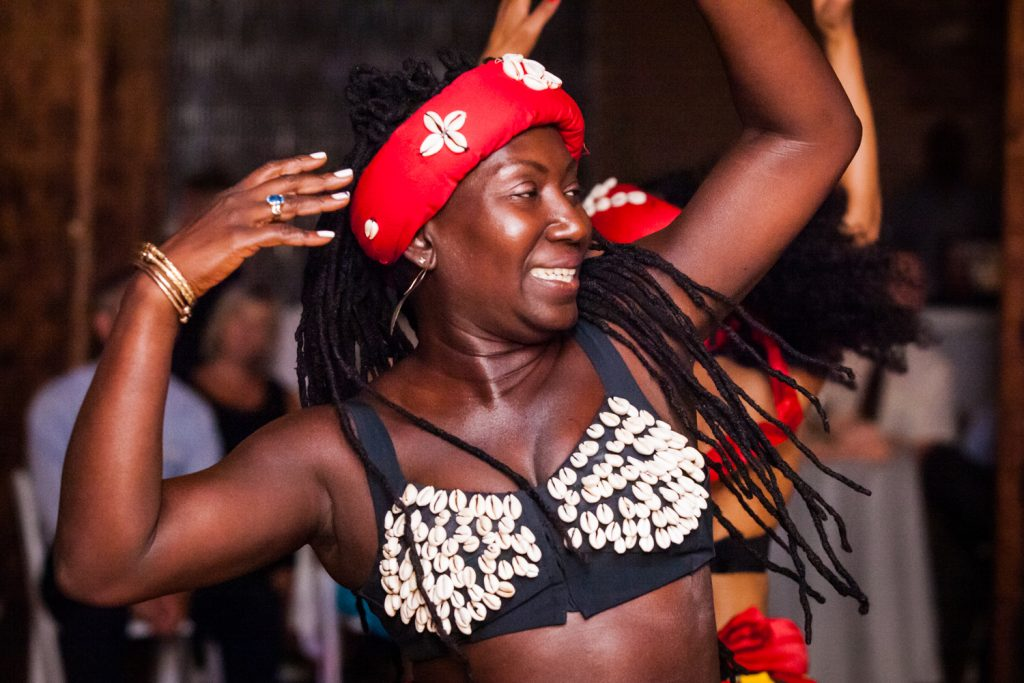Woman in African costume dancing with arms raised at a DUMBO Loft wedding