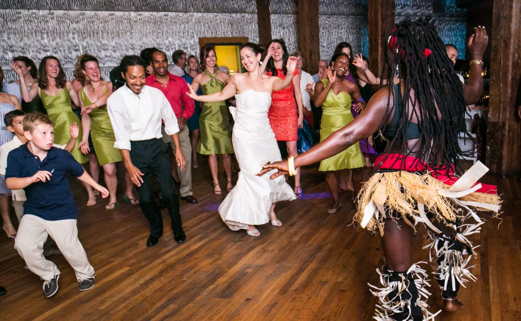 Bride and guests dancing with African dancer at a DUMBO Loft wedding
